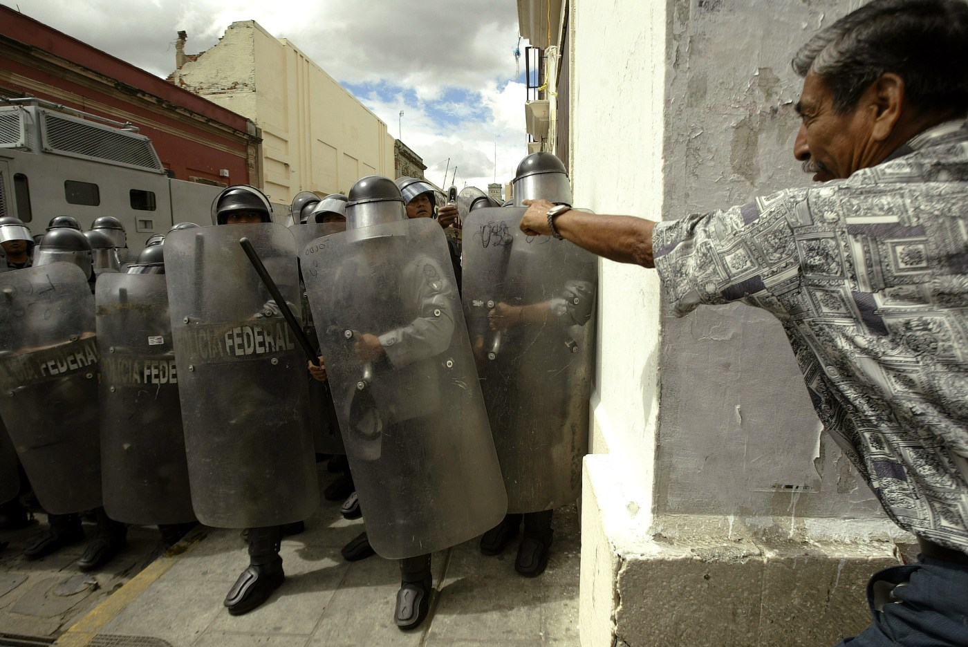 A protester confronts Mexican federal police officers as they guard Oaxaca's Zocalo Saturday, Nov. 4, 2006, in Mexico. Protests began in May with a strike by teachers demanding better pay and work conditions in one of Mexico's poorest states. When police violently broke up a demonstration in June, protesters expanded their demands to include Gov. Ulises Ruiz's resignation and were joined by leftists, Indian groups, students and others. (AP Photo/Guillermo Arias)