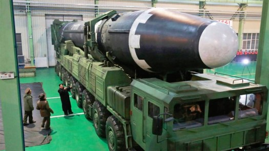 North Korean premier Kim Jong-un, in black, stands next to a Hwasong-15 ICBM ahead a test in November 2017.