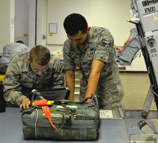 Airmen work on an ejection seat survival kit, which will now contain a break-apart rifle.