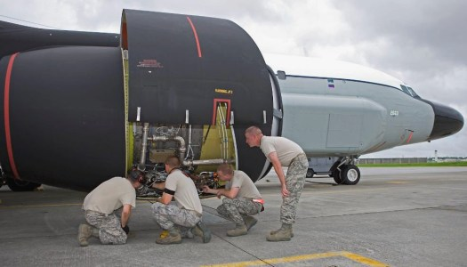Air Force ground crew personnel inspect one of the engines on an RC-135S Cobra Ball.