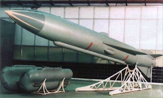 A P-70 anti-ship missile on a display stand with its rocket booster on a separate rack in the foreground.