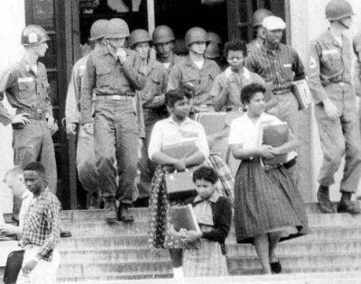 Minnijean Brown Trickey, right, and others of the Little Rock Nine leave Central High School under troop escort in September 1957. Photo: National Park Service.