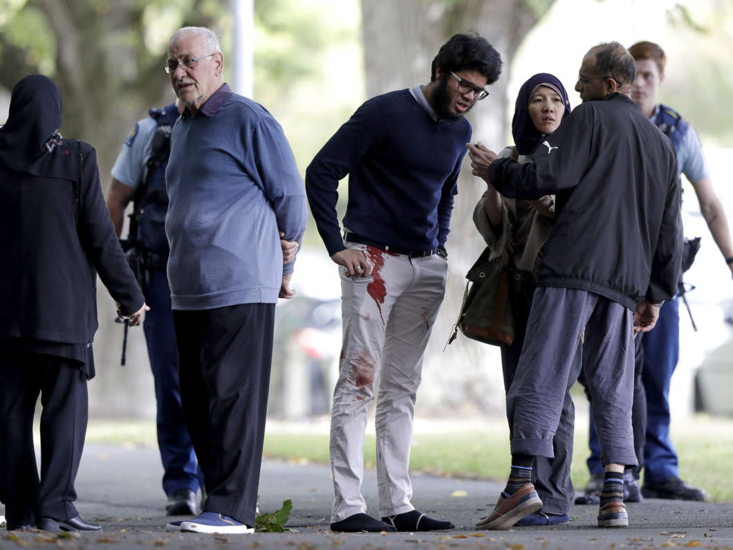 People stand across the road from a mosque in central Christchurch, New Zealand, following shootings at two mosques that killed 49 people on Friday.