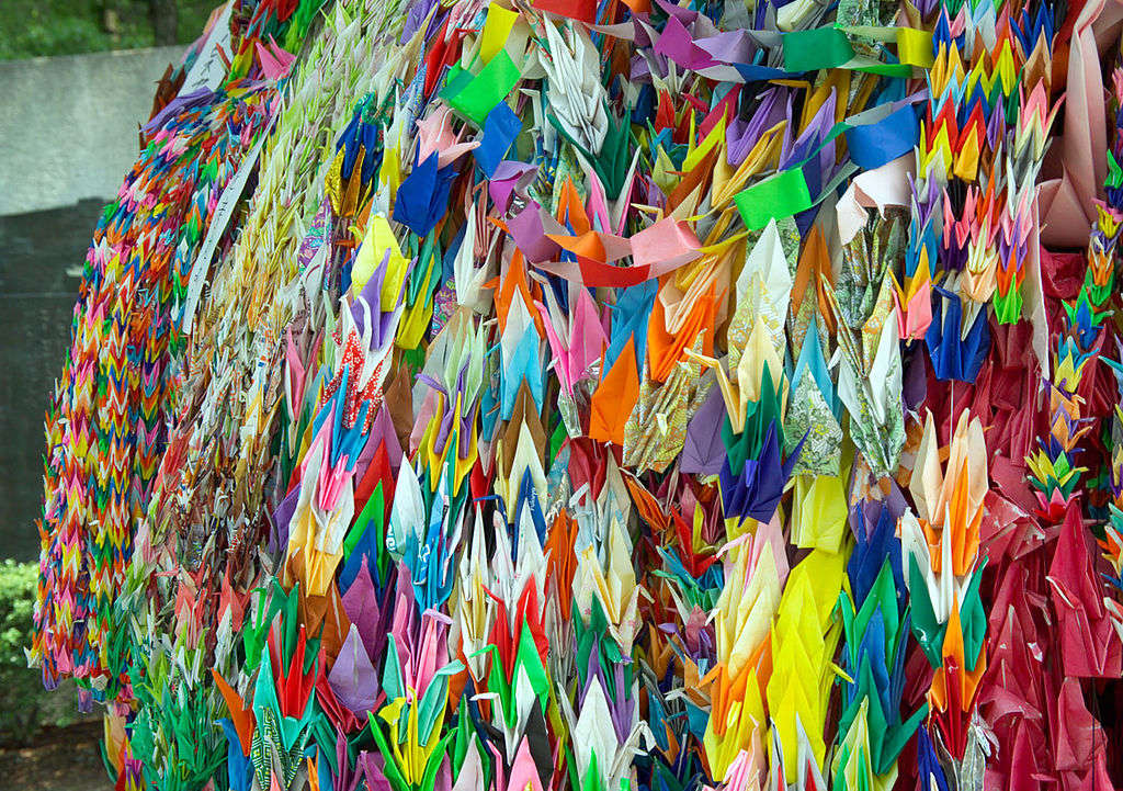 Photo: Paper cranes, folded as prayers for peace. Peace Park, Hiroshima, Japan. Courtesy of Fg2, Wikimedia Commons