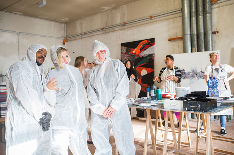 IMAGE: Three designers in paint-protective onesies