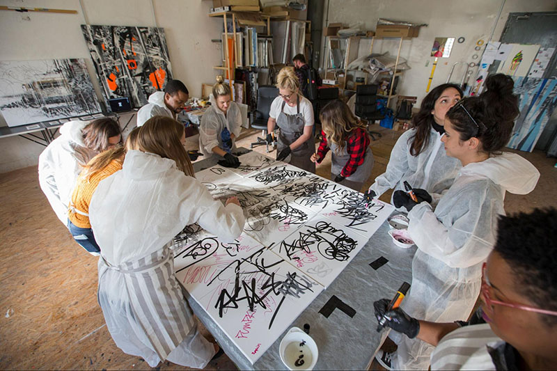 IMAGE: Designers in head-to-toe paint-protector onesies surrounding a canvas
