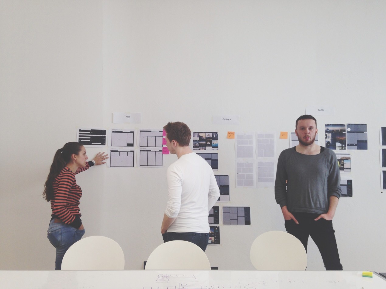 IMAGE: Three people wireframing on a wall