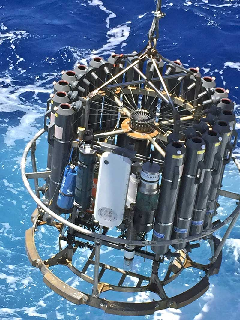 """Researchers lower a """"rosette package"""" to the bottom of the ocean to gather water samples. (NOAA)"""