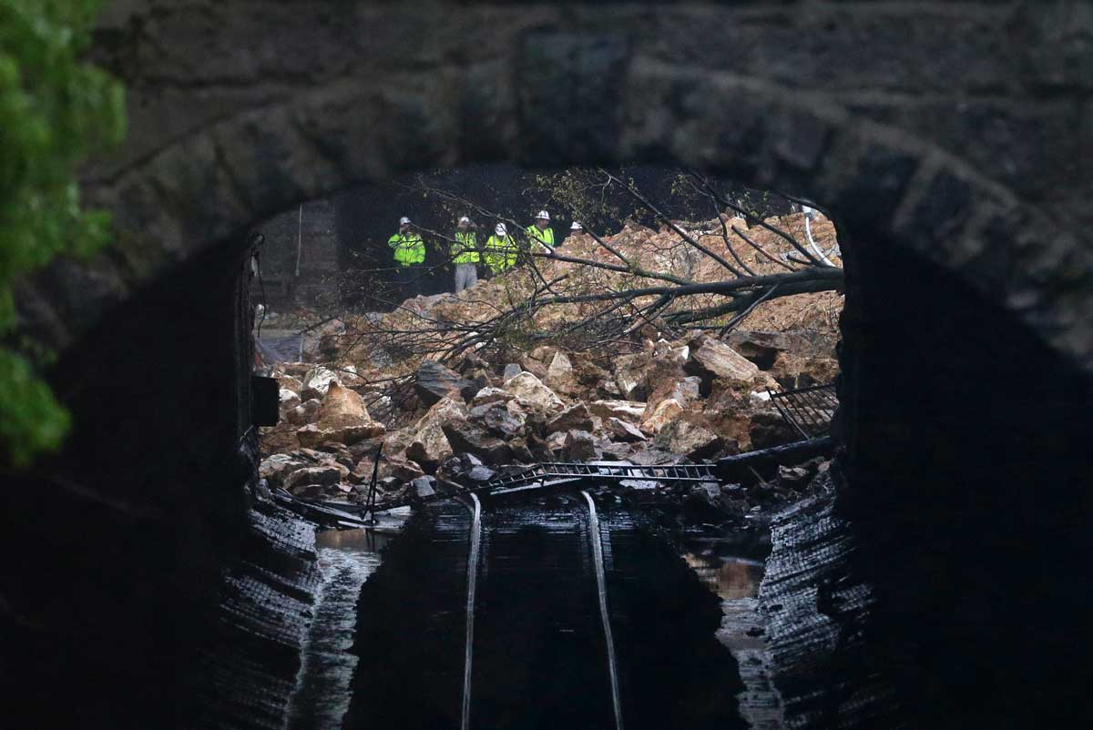 Emergency officials are seen through a CSX railroad tunnel near debris that fell onto tracks in the Charles Village neighborhood of Baltimore, Wednesday, April 30, 2014, as heavy rain moves through the region. (AP Photo)