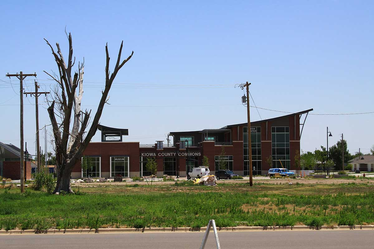 A vision of the past, and the future – the rebuilt Kiowa County Commons building is seen behind the remains of a tree damaged by the tornado. (Flickr/Kansas Tourism)