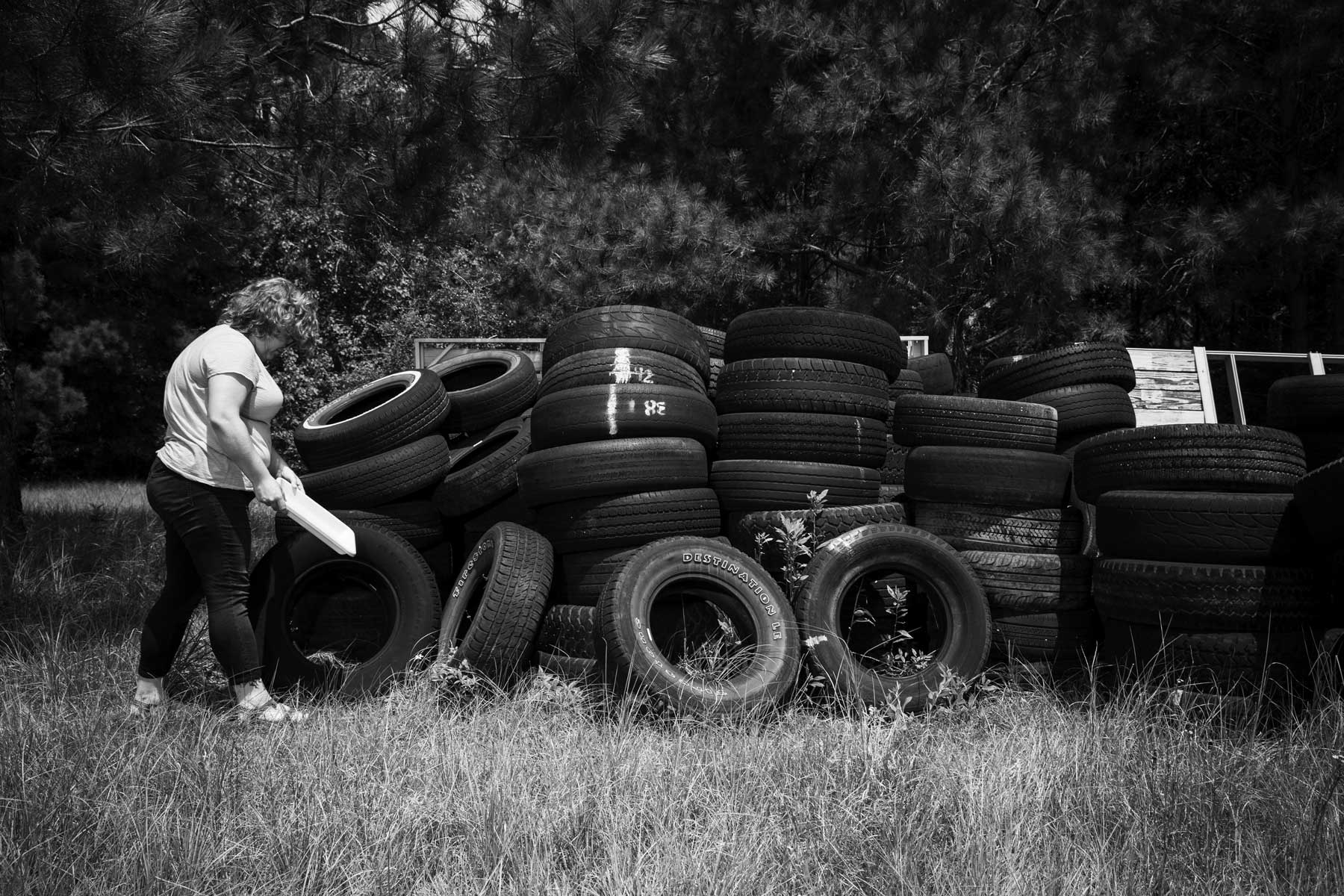 Catherine Dean, 23, a graduate student, checks standing water from inside of tires for larvae of the Asian tiger mosquito at a research facility at the University of Southern Mississippi in Hattiesburg.