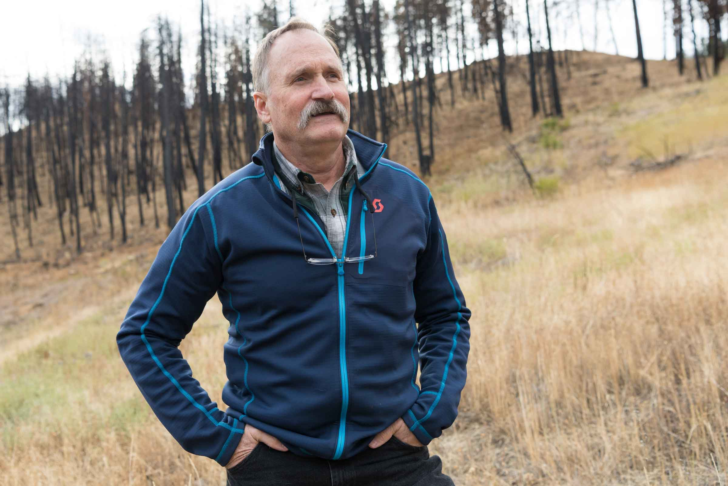 """Paul Hessburg ponders solutions to the megafire epidemic as he stands on land burned by the 2015 Canyon Creek Complex megafire south of John Day. """"Burn under the right conditions is a big core of the answer,"""" he says. """"We're not going to [mechanically] thin our way out of this problem. There isn't enough time. It's changing the landscape too fast."""" (Adam Bacher)"""