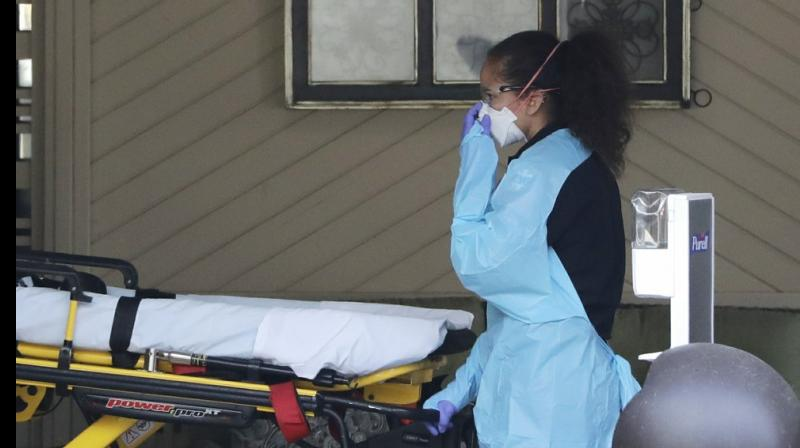 An ambulance worker adjusts her protective mask as she wheels a stretcher into a nursing facility where more than 50 people are sick and being tested for the COVID-19 virus. AP Photo