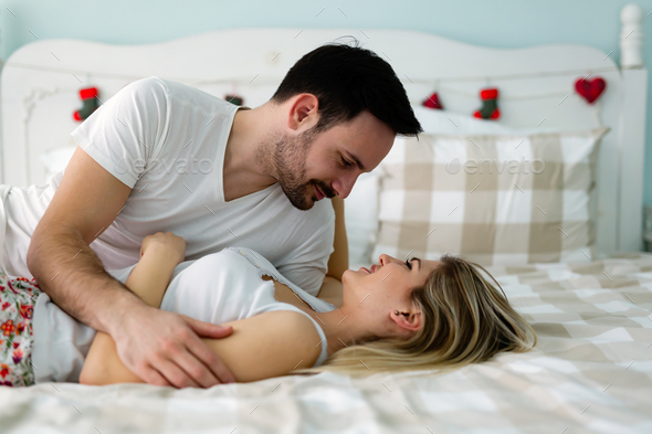 Young attractive couple having romantic time in bed Stock Photo by nd3000