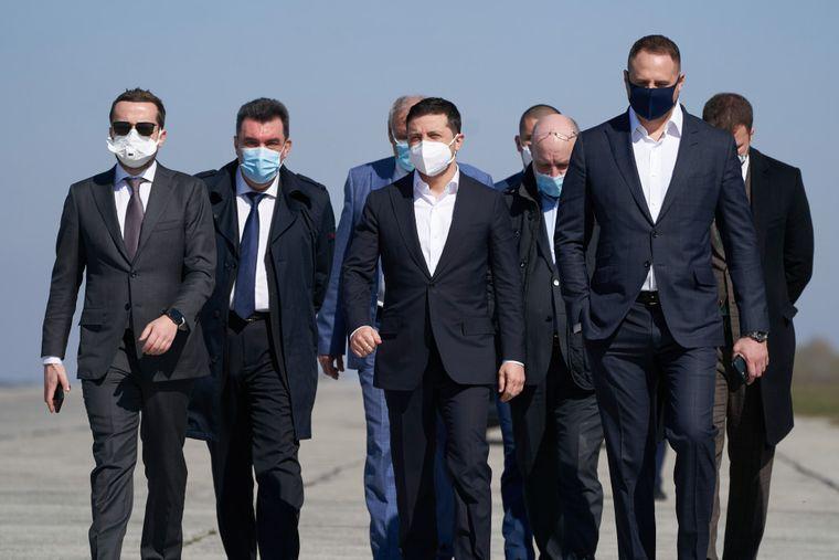 Президент України Володимир Зеленський (в центрі), і представники Офісу президента в масках для захисту від коронавірусу зустрічають вантажний літак з Китаю з гуманітарною допомогою в аеропорту Гостомель у Києві, Україна, 23 квітня 2020 року.