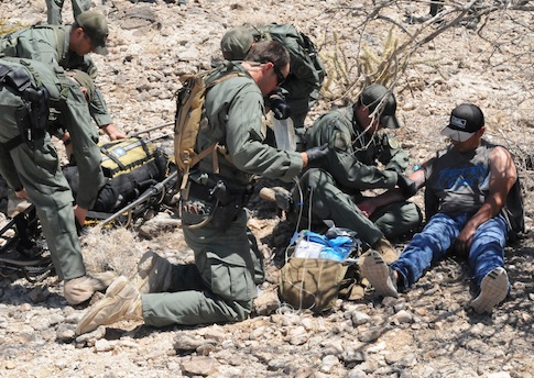 Border Patrol Rescue Team administers an I.V. to help an illegal border crosser. / AP