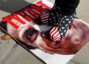 A member of NY2A Grassroots Coalition, stands on an image of New York Gov. Andrew Cuomo / AP