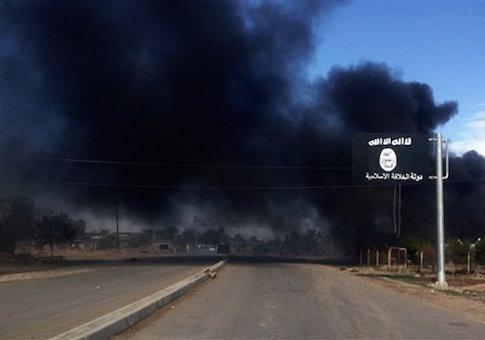 Olas de humo detrás de un signo grupo Estado Islámico