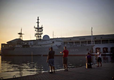 Men fish near the Russian warship Viktor Leonov CCB-175, docked in Havana's harbor, Cuba, Wednesday, Jan. 21, 2015