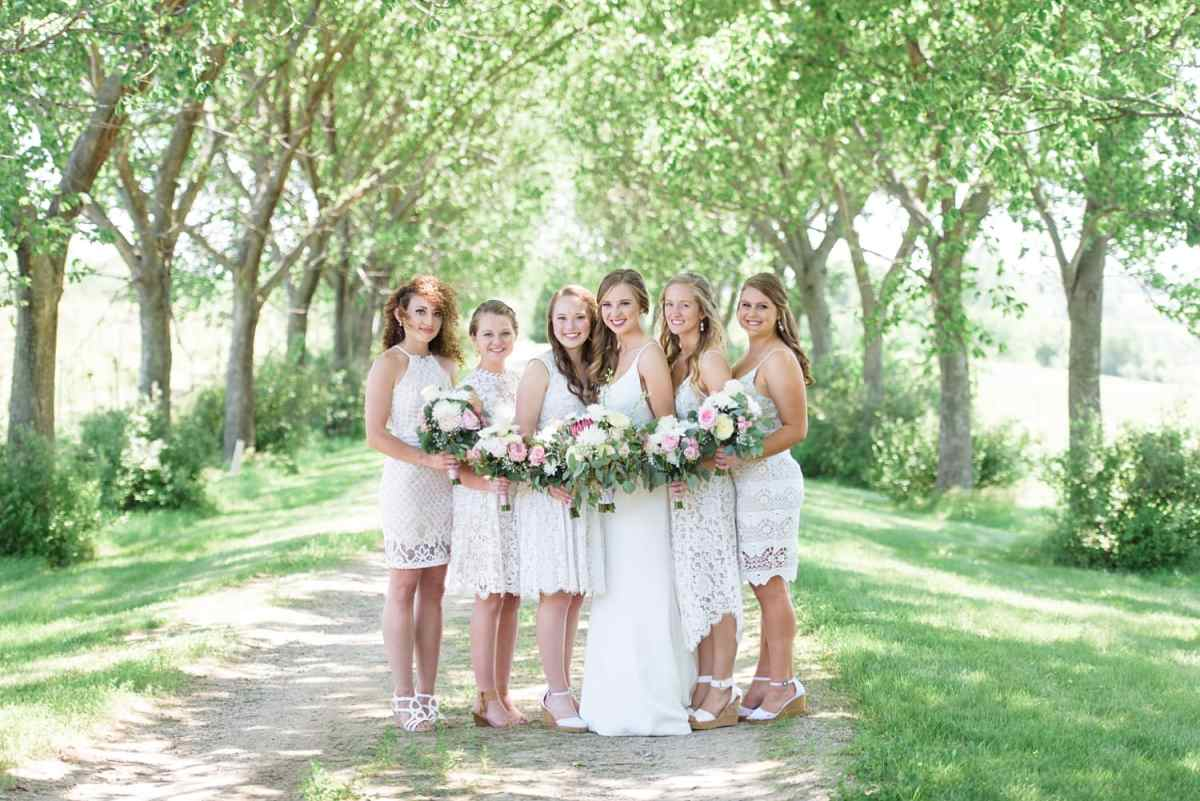 bridesmaids wearing ivory lace dresses for photos on oak lined lane at Sugar Grove vineyard in Iowa