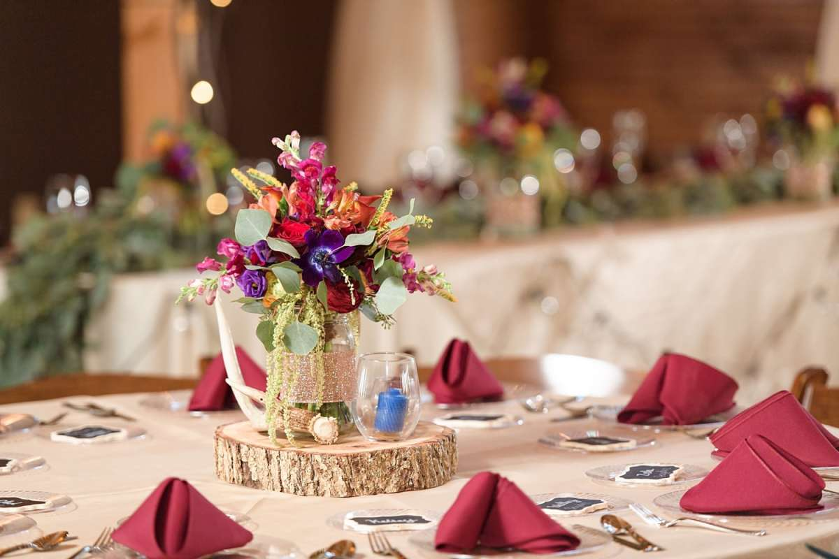 sugar grove fall wedding reception table centerpiece with antlers and burgundy florals