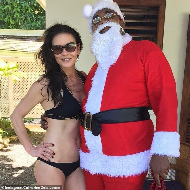 Navidad: Catherine Zeta-Jones marcó el día de Navidad compartiendo una foto festiva de ella misma posando en un pantalón de dos piezas negro con Santa Claus en las Bermudas el año pasado.