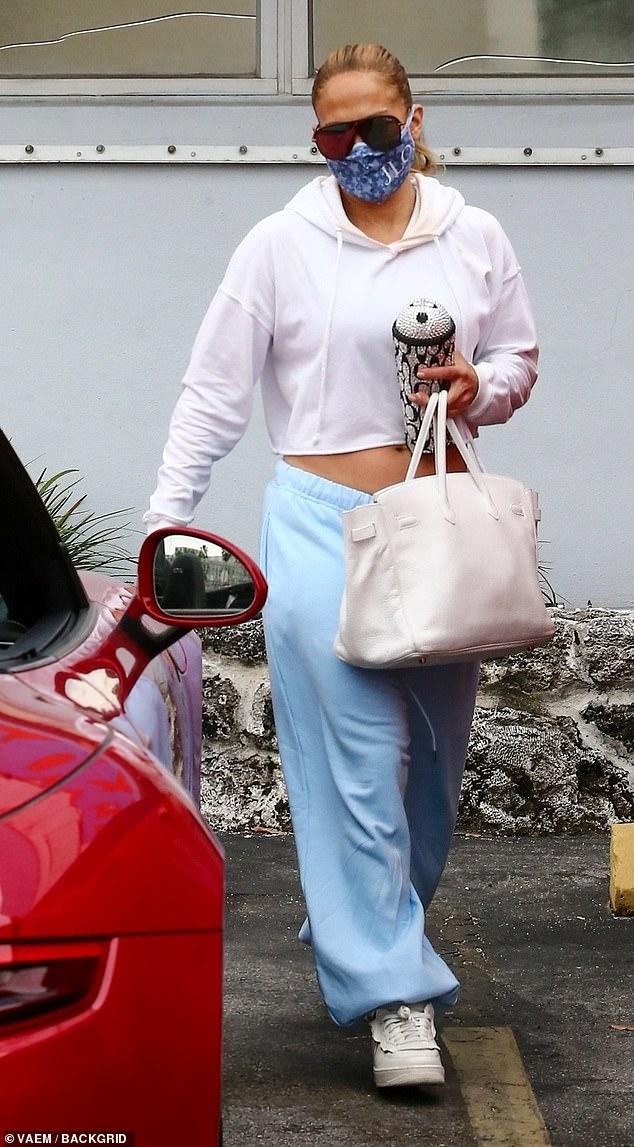 De vuelta a casa: Jennifer Lopez mostró un pequeño estómago y mostró su bronceado mientras se dirigía a Miami el martes después de unas vacaciones en Turks & Caicos.