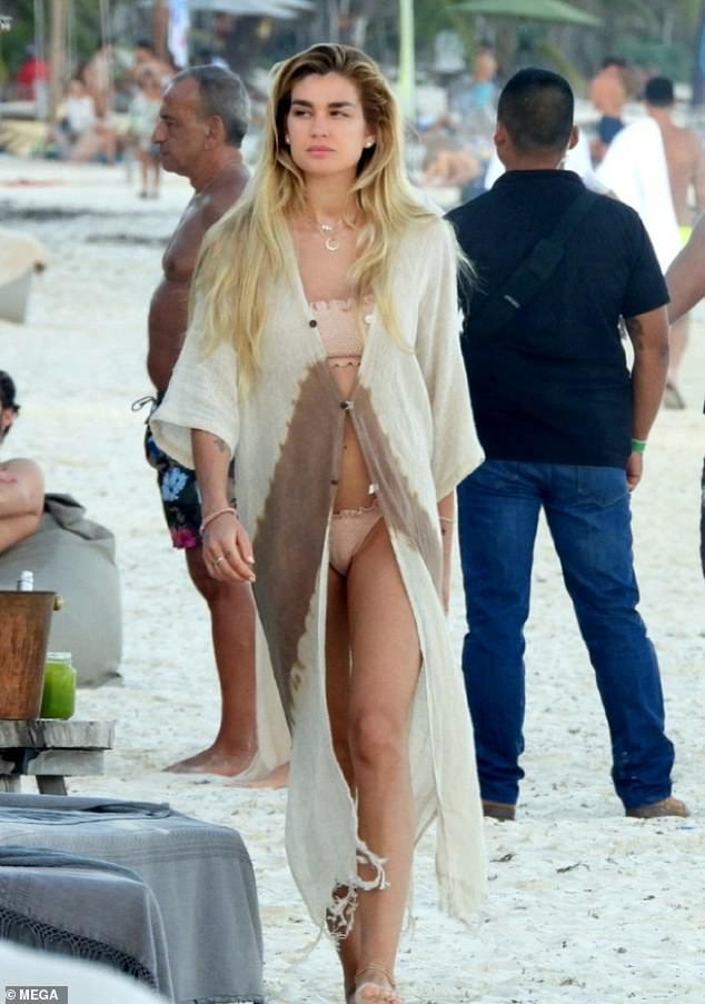 Día de playa: Shayna Taylor, de 28 años, cubrió su físico en forma con un vestido de playa beige mientras paseaba por la arena en Tulum, México, el viernes.