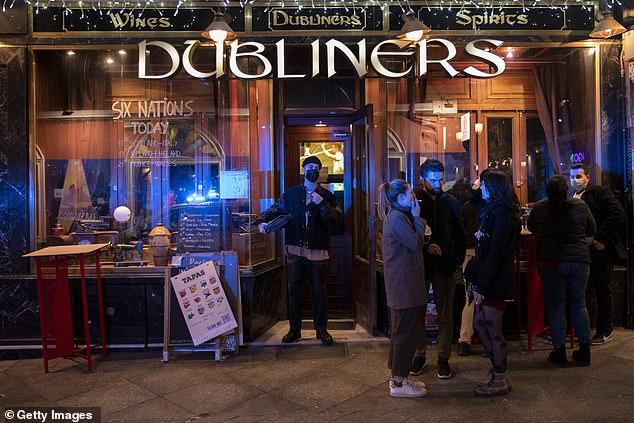 Los turistas se paran afuera de un bar mientras comienza el toque de queda durante la pandemia de Coronavirus el 20 de marzo de 2021 en Madrid.