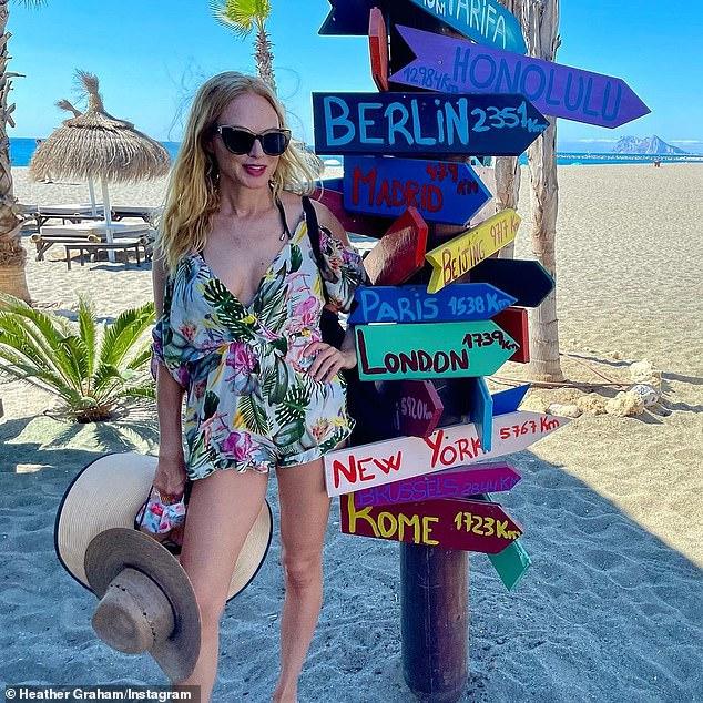 Encubrimiento coqueto: la alumna de Boogie Nights, Heather Graham, lucía de piernas largas con un mameluco tropical mientras hacía turismo en una playa en el sur de España el martes