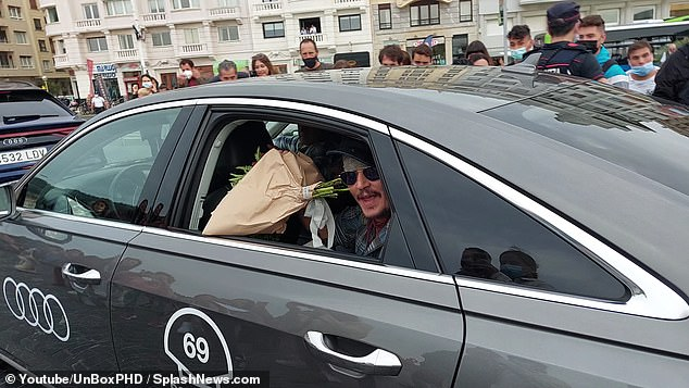 Sweet gesture: Johnny Depp was gifted flowers by a fan through his car window as he left the San Sebastian Film Festival on Thursday (pictured) amid claims Hollywood is 'boycotting' him due to $50m defamation lawsuit