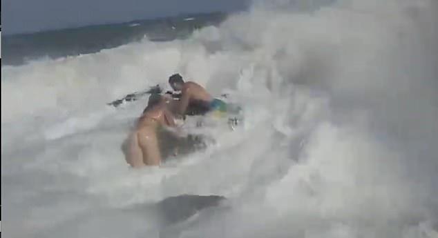 Las imágenes muestran el momento conmovedor en el que el ruso Daniil Gagarin, de 30 años, se sumerge en las agitadas aguas en un intento por rescatar a Emma Monkkonen, de 24 años, de Finlandia (en la foto juntos aferrándose a una roca)