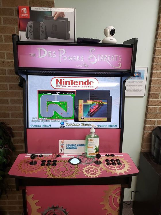 A pink arcade game in the reception for the LGBT+ friendly medical clinic. On top there is a Switch game console.