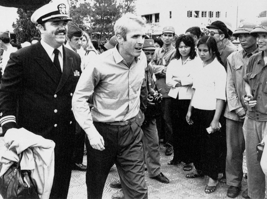 In this March 14, 1973, file photo, U.S. Navy Lt. Cmdr. John McCain, center, is escorted by Lt. Cmdr. Jay Coupe Jr., to Hanoi, Vietnam's Gia Lam Airport, after McCain was released from captivity.