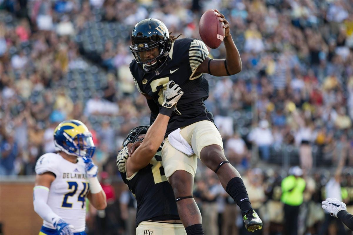 Wake forest demon deacons quarterback kendall hinton gets lifted in the air after  touchdown during first quarter against delaware fightin blue also football top fall camp position battles rh sports