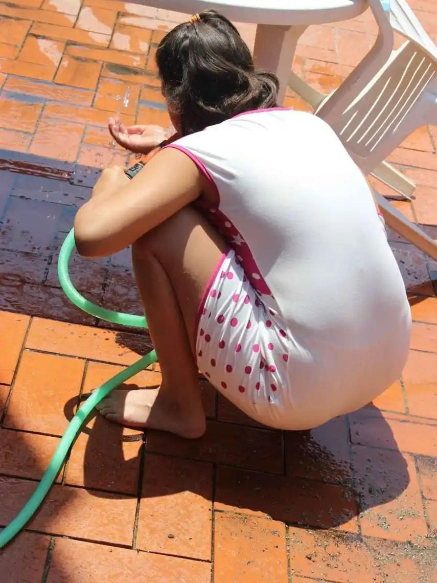 Elia, que en noviembre cumplirá 15 años, se refresca con una manguera en el patio de su casa