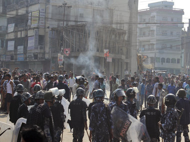 Ethnic Madhesi protesters stand near smoke from a tire set on fire by them, as Nepalese policemen stand guard at Birgunj, a town on the border with India. AP