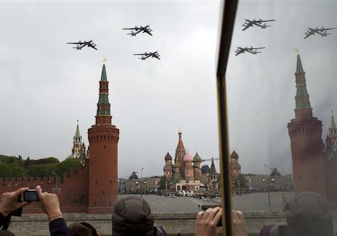 People watch as Russia's Air Force strategic bombers, Tu-95, fly over Red Square during a rehearsal for the Victory Day military parade