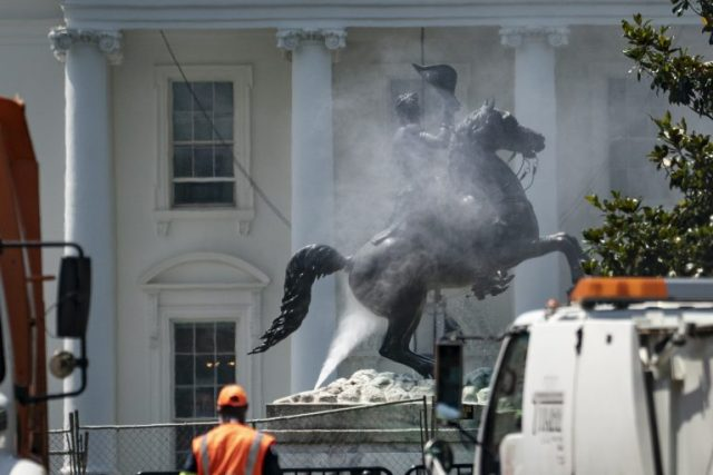 Workers clean the statue of Andrew Jackson in Lafayette Square