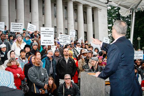 Ross' bald spot addresses the Refugee Women's Association on the Capitol steps