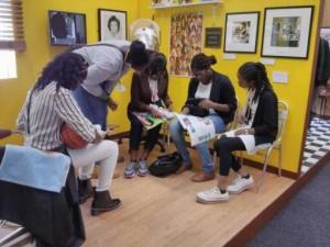 Girls flip through old magazines detailing African hair styles