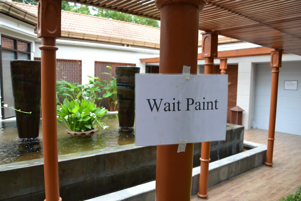 Sign saying Wait paint instead of wet paint Translation Toubon Law