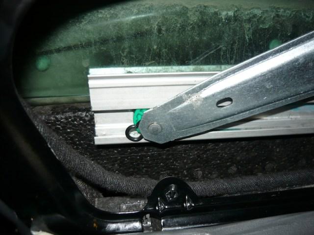 Figur: glidbussning. Fästet, från vilket bågen kan ses här, fixerar rullen på axeln (axeländen syns som en rund cirkel på fönsterhandtaget).