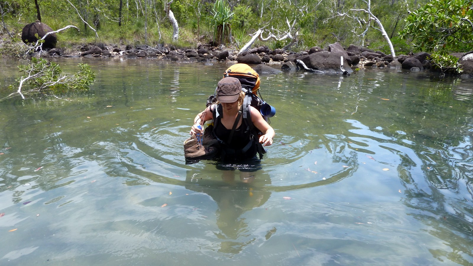 this is a photo of a hiker in Hinchinbrook Island wading through hip deep water