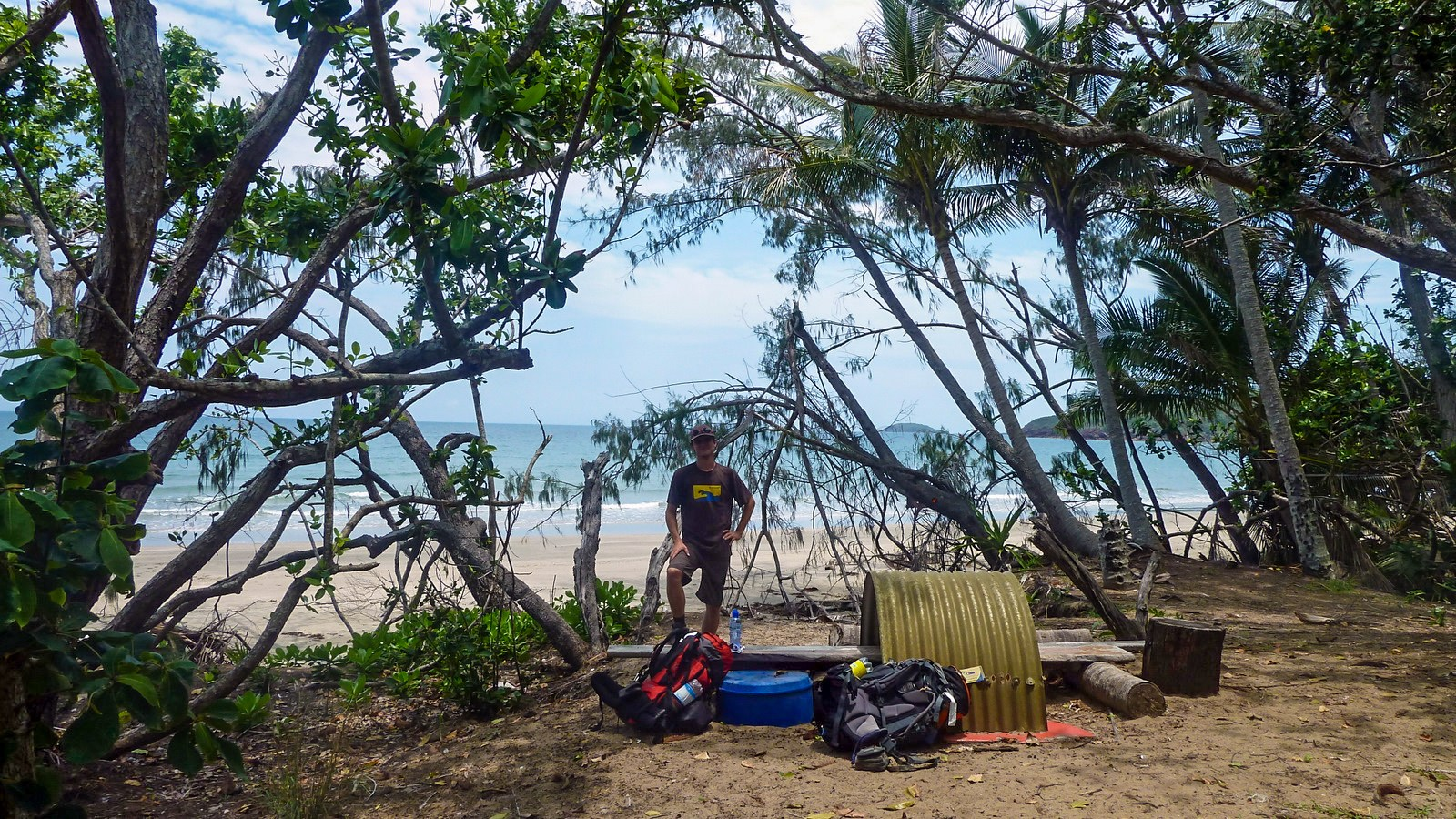 this is a photo of a hiker taking a break at a shady spot close to the beach of hinchinbrook island