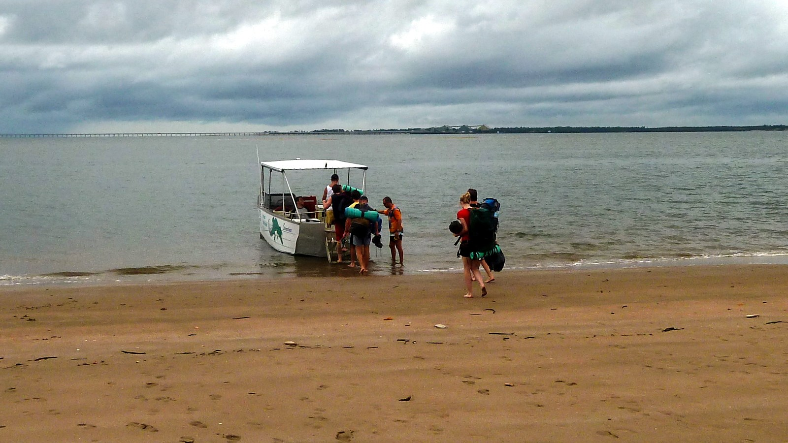 a photo of hikers getting picked up by the ferry on hinchinbrook island.