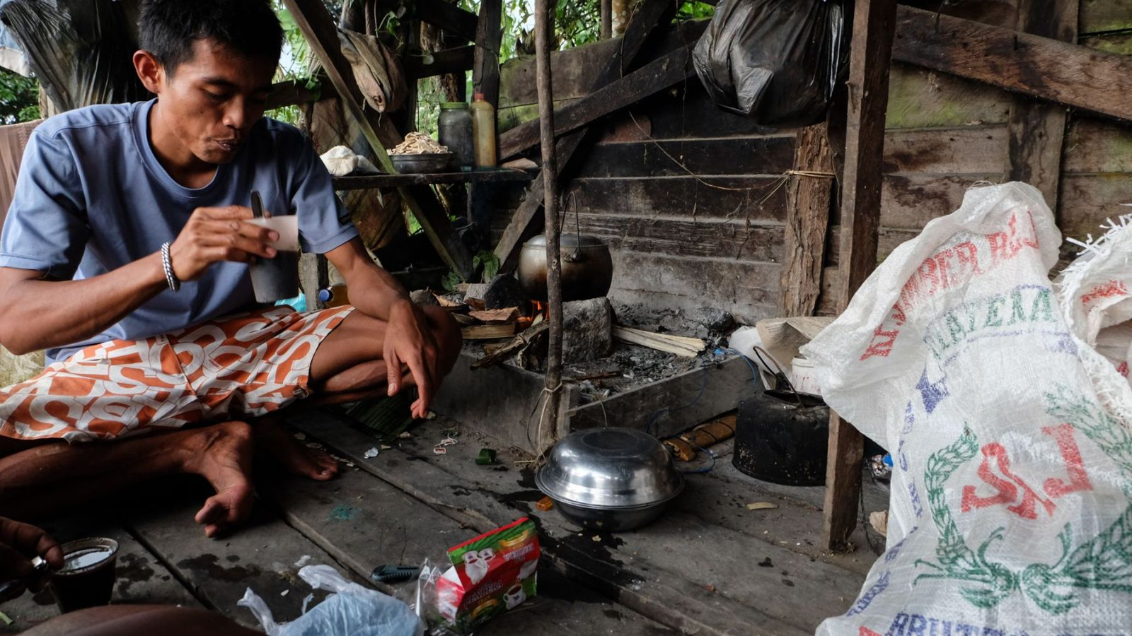 photo of a former rebel hut in gunung leuser national park and a person preparing food.