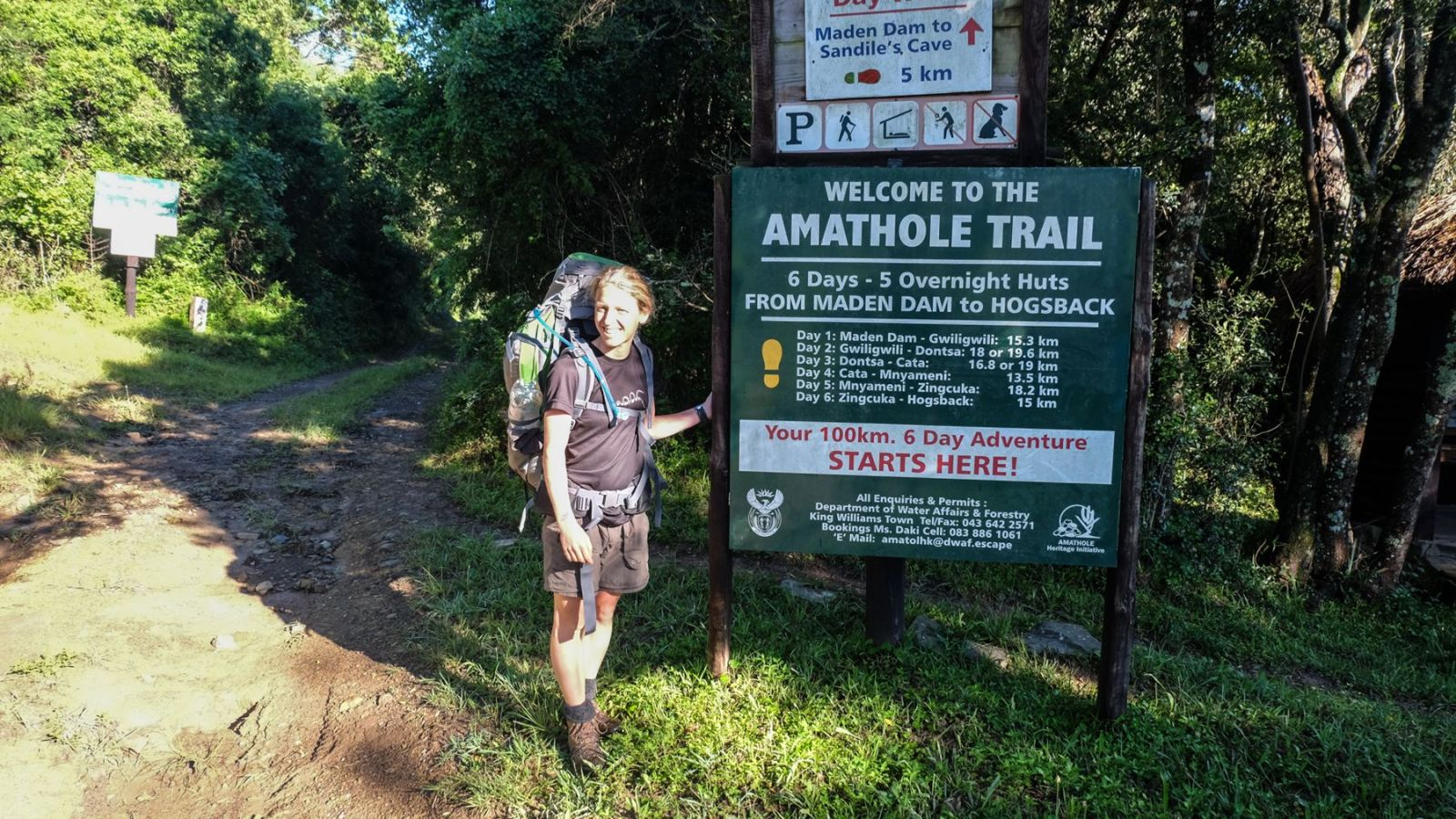 a photo of a hiker next to the sign post for distances on the amathole hiking trail.