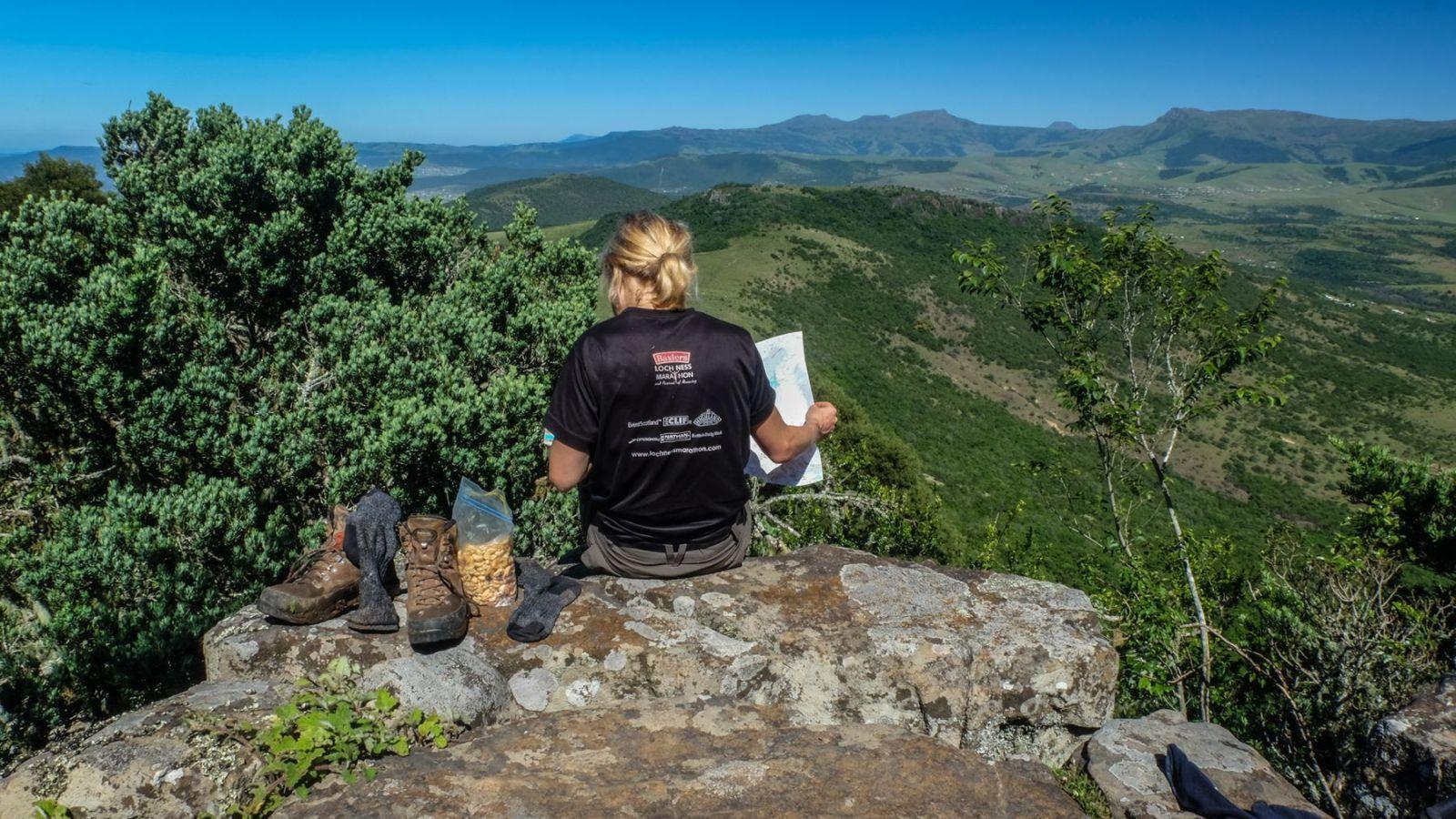 a photo of a hiker reading the map on the amathole hiking trail.