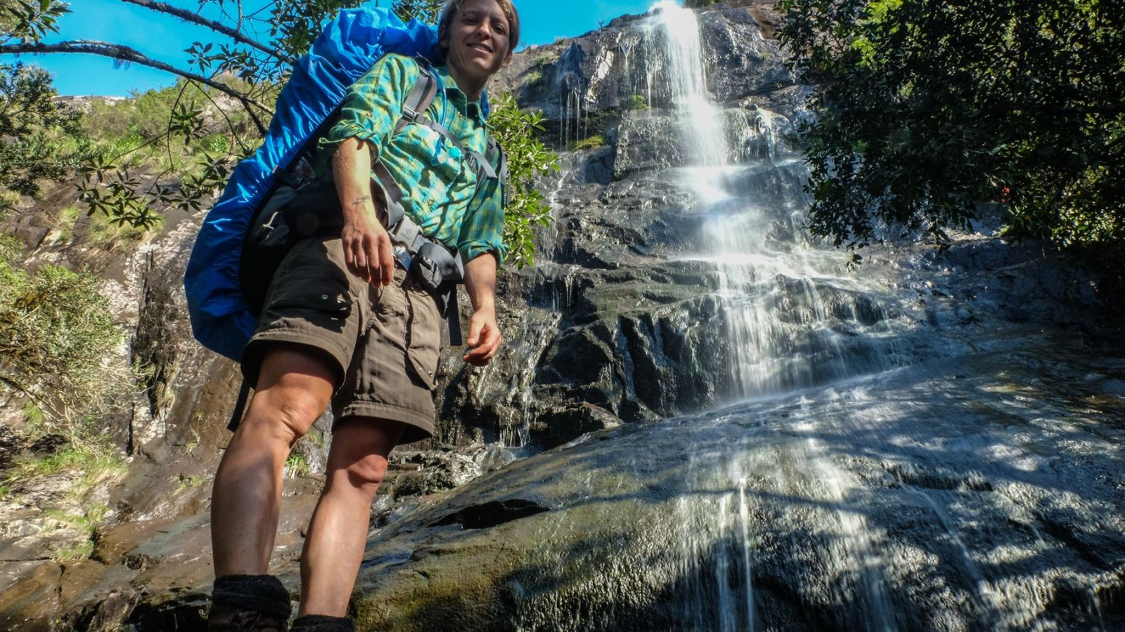 a photo of a hiker in front of a waterfall on the amathole trail.